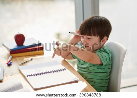 Little boy making notes in his textbook