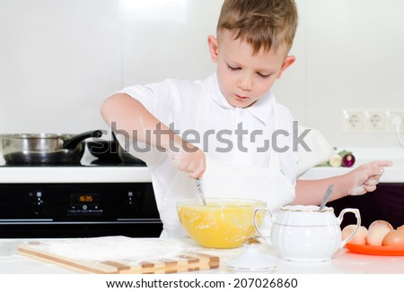 Little boy mixing cake ingredients in a mixing bowl whipping the flour and eggs to make the dough - stock photo