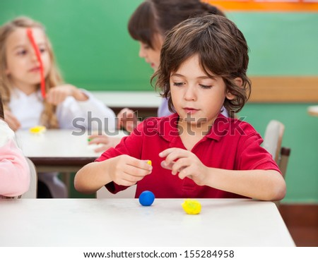 Little boy molding clay with female friend in background at classroom - stock photo