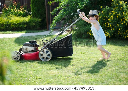 little boy mows lawn with mower