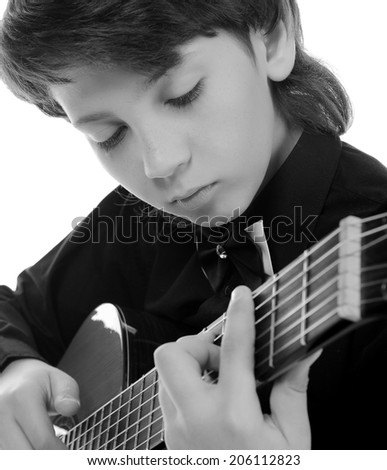 Little boy musician playing on acoustic guitar. Isolated on a white background