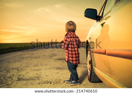 little boy near car at rural road to sunset - stock photo