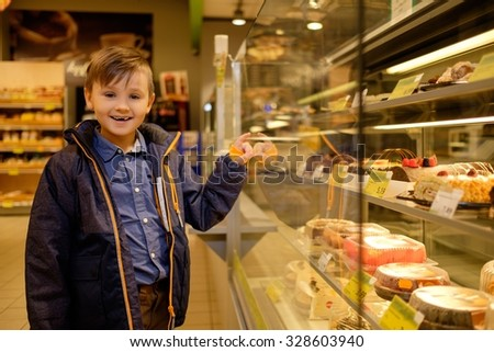 Little boy near display with cakes in a grocery store  - stock photo