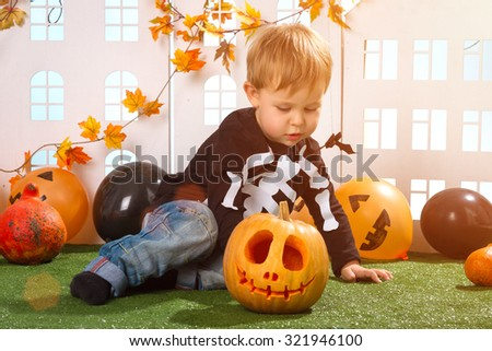 Little Boy Near Halloween Pumpkin And Little White Houses  - stock photo