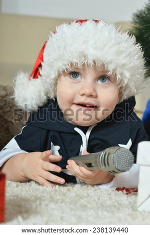 Little boy near new-year tree with microphone - stock photo