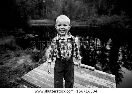 Little boy near the lake - stock photo