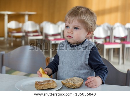 Little boy of one year eating bread and apple in playschool for breakfast