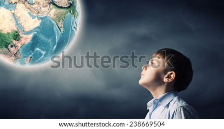 Little boy of school age looking at Earth planet. Elements of this image are furnished by NASA - stock photo