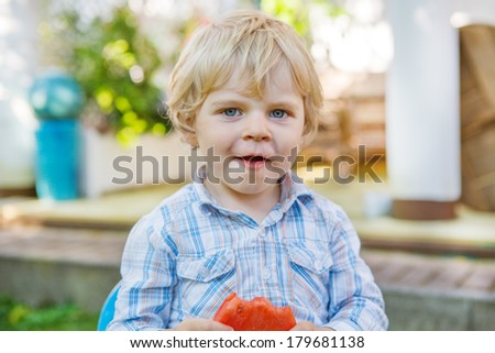 Little boy of two years eating fresh healthy watermelon in summer garden. - stock photo