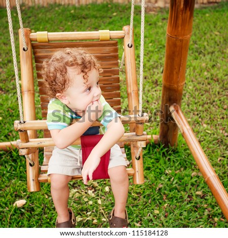 little boy on a bamboo swing - stock photo