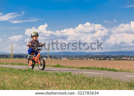 Little boy on a bicycle for the first time. Small child learns to ride a bike. Safe Driving preschool child with a helmet.