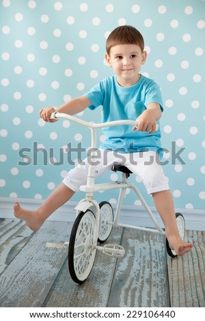 little boy on a bicycle in the room - stock photo