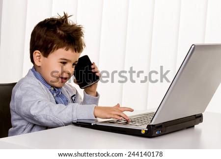 little boy on a laptop, symbol of the internet, e-commerce, consumer behavior - stock photo