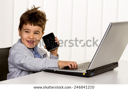 little boy on a laptop, symbol of the internet, e-commerce, consumer behavior - stock photo