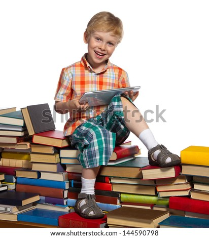 Little boy on a pile of books holds a tablet computer in his hands.