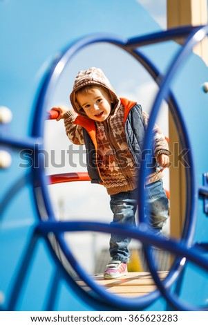 Little boy on a playground. Child playing outdoors in summer.Children having fun at daycare play ground.