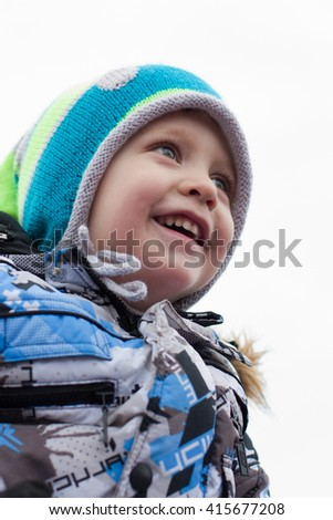 little boy on a winter walk looks up and laughs - stock photo