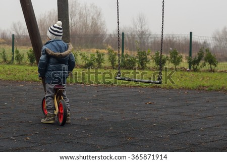 Little boy on a wooden bicycle - stock photo