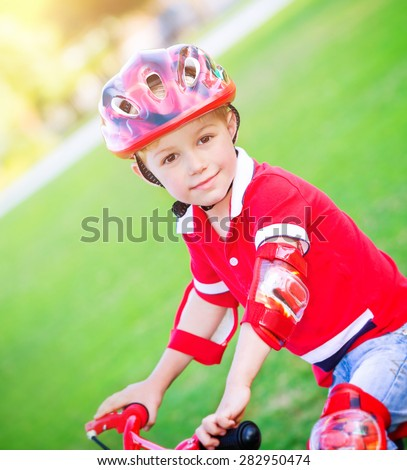 Little boy on bicycle wearing red protective helmet, having fun on backyard, active childhood, enjoying cycling, summer holidays