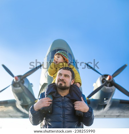Little boy on his father's shoulders, looking away. Against the background of the spiral plane. - stock photo