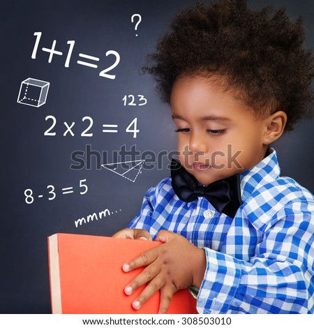 Little boy on math lesson, holding in hands book and standing near blackboard with written mathematical equation, back to school - stock photo