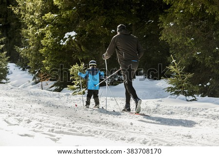Little boy on skis with father on a running track in the woods. He pushed a running wand - stock photo