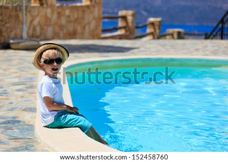 little boy on summer vacation by the pool - stock photo