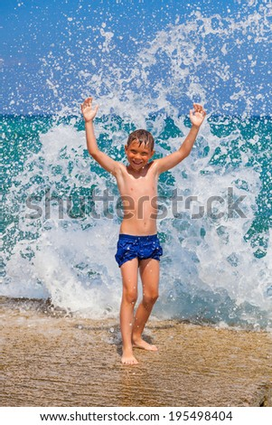 Little boy on the beach with big splashes on background - stock photo