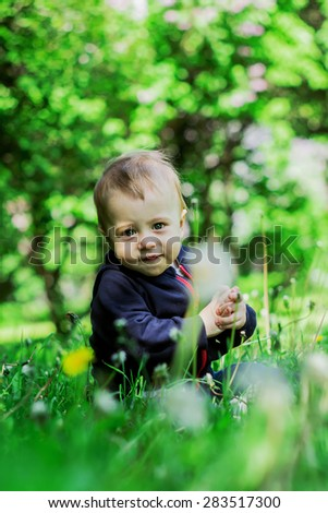 Little boy on the beautiful green lawn with dandelions. Image with selective focus - stock photo