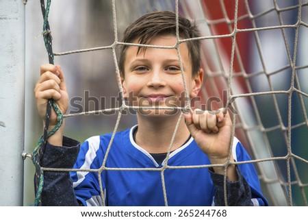 Little boy on the football stadium, close-up portrait. - stock photo