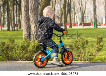 Little boy on the run bike from the back