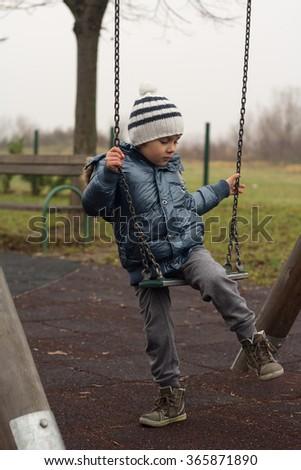 Little boy on the swing - stock photo