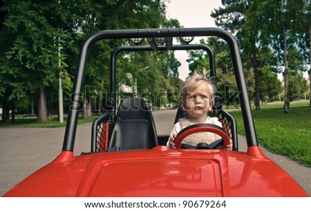 little boy on the toy electric car in the park - stock photo