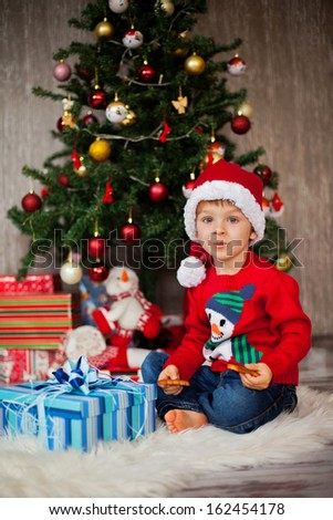 Little boy, opening presents on christmas