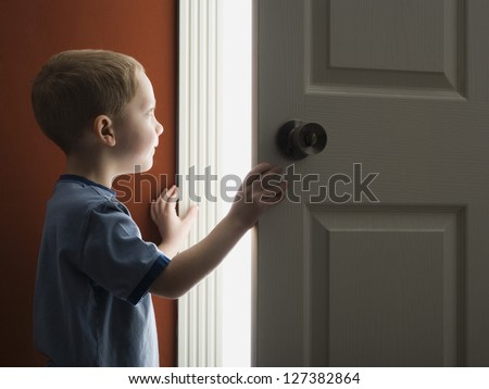 Little boy opening the door at home - stock photo