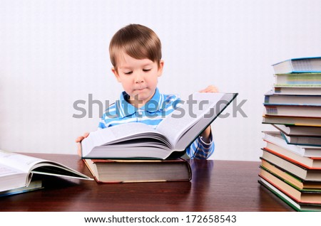 little boy opens a large book and looking into it boy 5 years. on the desk a lot of books. photo taken on a light background