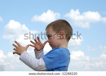 Little boy over cloudy blue sky showing long nose - stock photo