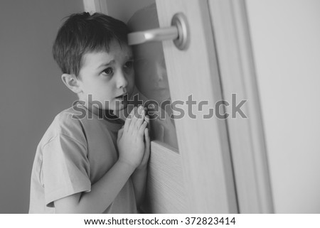 Little boy overhears fight of his parents through the door - black and white - stock photo