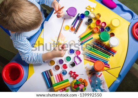 little boy painting at the table with art supplies, top view - stock photo