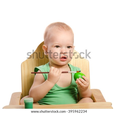 Little boy  painting egg isolated on white
