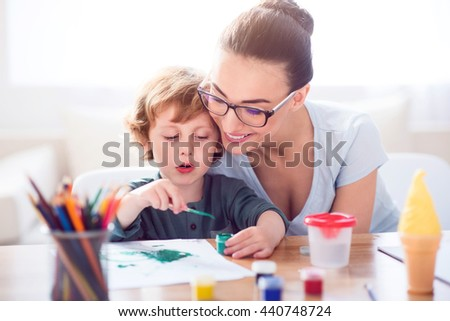 Little boy painting picture for mother - stock photo
