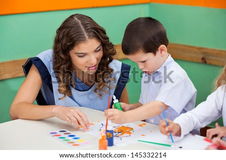 Little boy painting while teacher assisting him at classroom desk - stock photo
