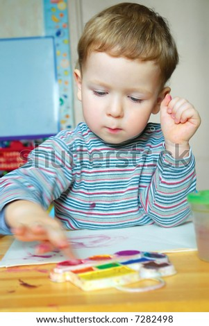 little boy painting with his finger
