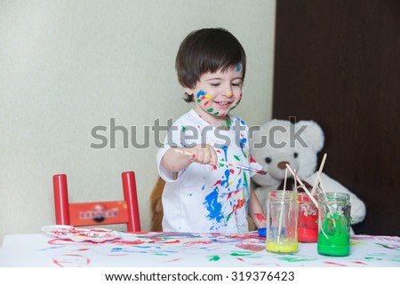 Little boy painting with paintbrush and colorful paints. Child painting.Young painter