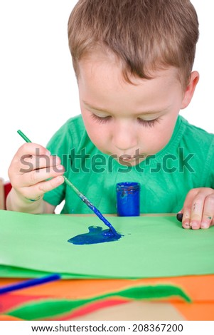 little boy paints with blue color and brushes