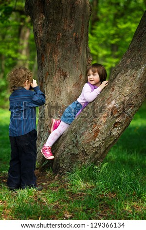 little boy photographing girl in the park on tree - stock photo