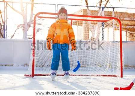 Little boy play hockey standing in gates  - stock photo