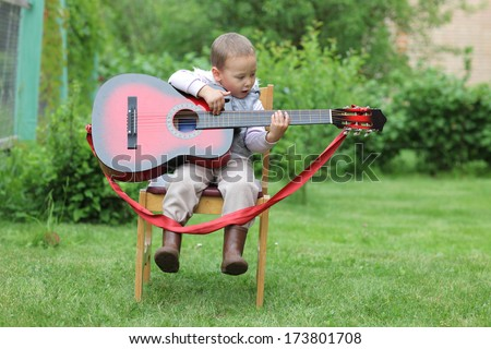 little boy play in guitar outdoors - stock photo