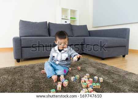 Little boy play toy block at home - stock photo