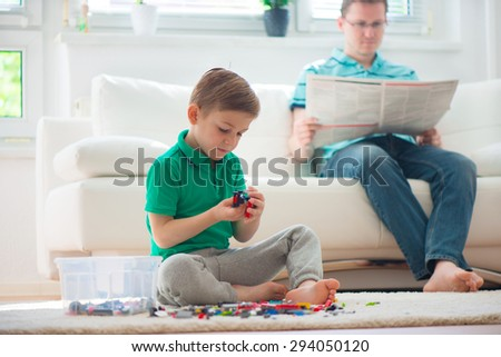 Little boy play with building kit, father read newspaper